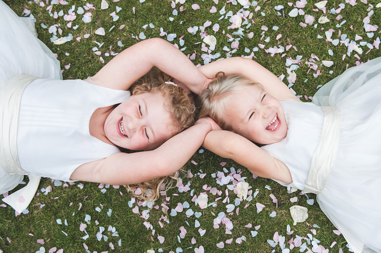 jma-photography-flowergirls-laying on-confetti-laughing.jpg