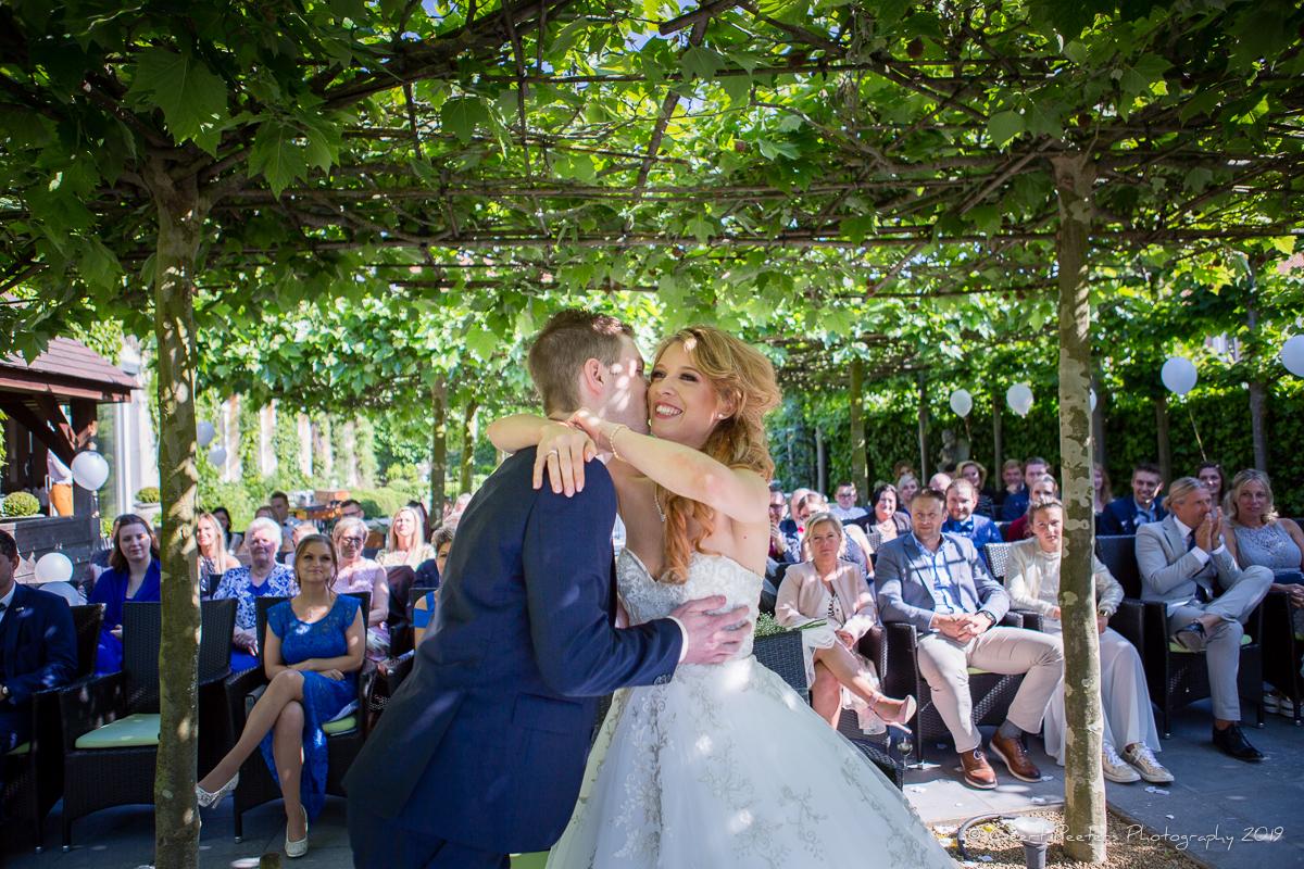 bruid en bruidegom kussen  in buiten ceremonie