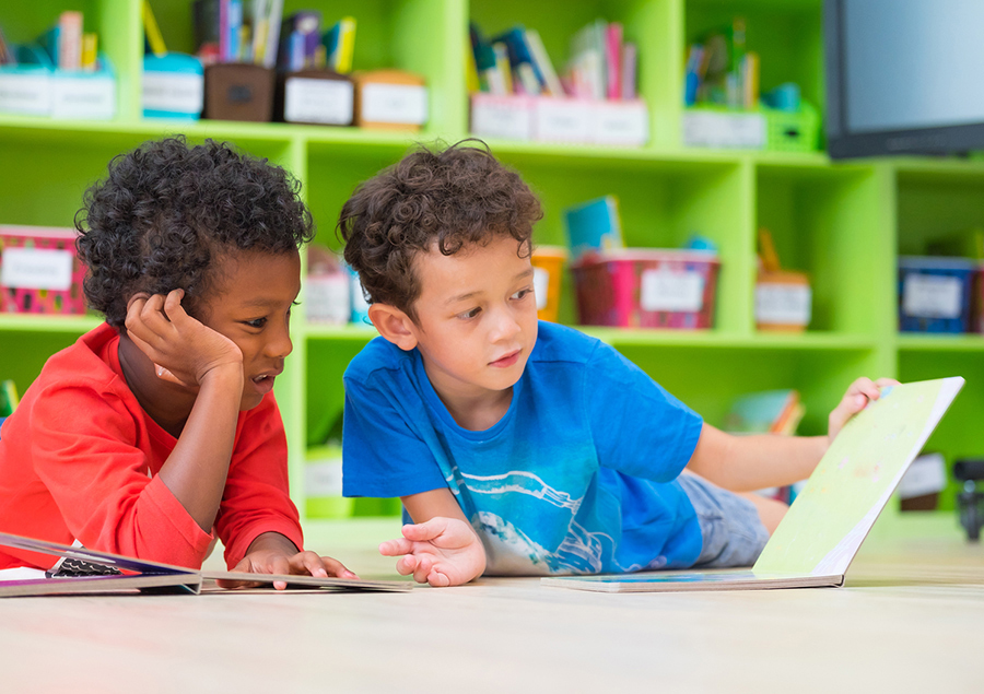 two boys reading a children's book