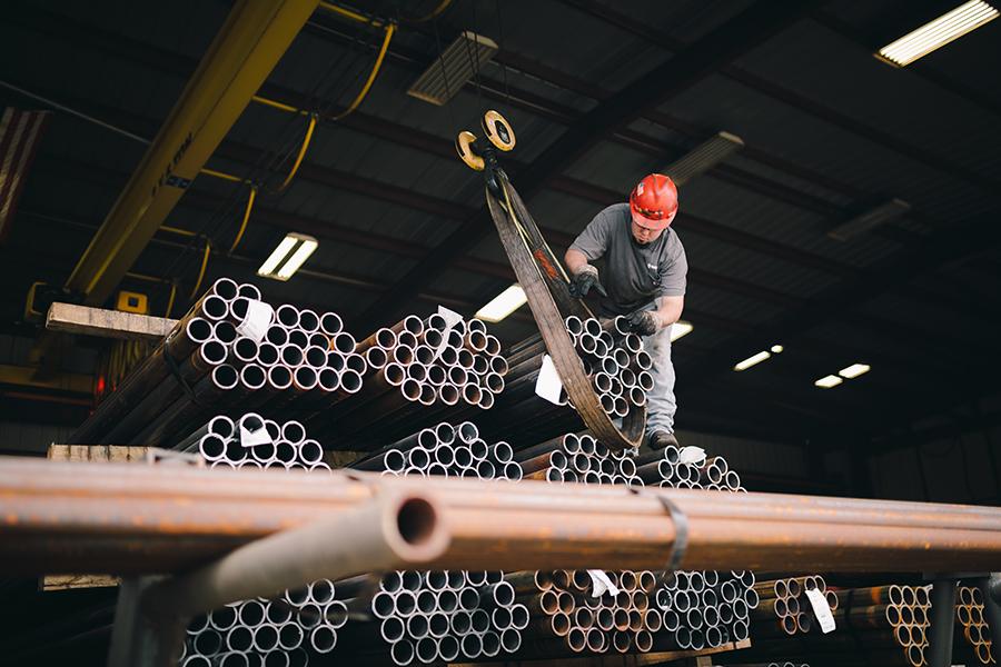 Ramjack employee lifting metal pipes