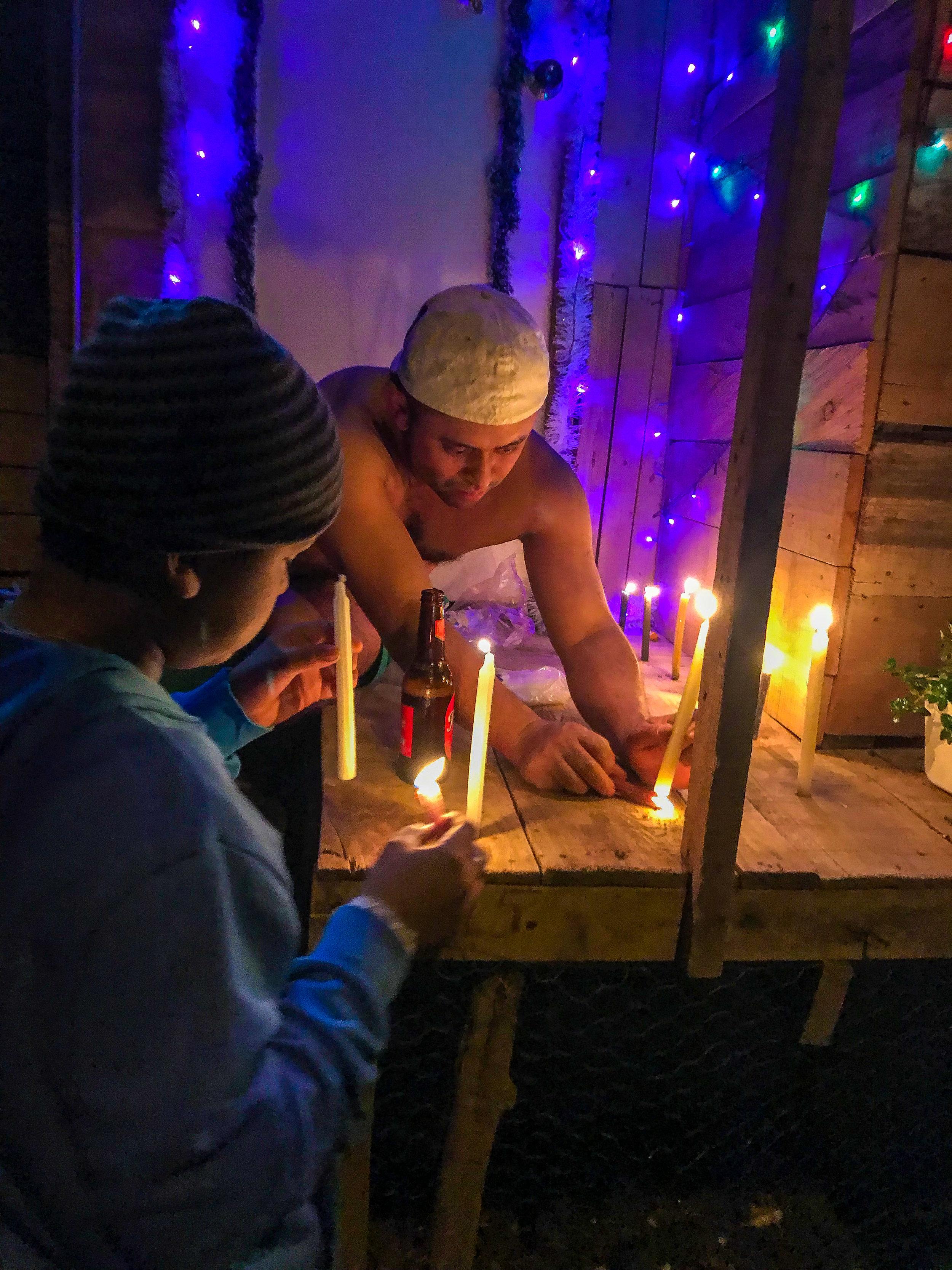 Father and son lighting candles for Día de las Velitas