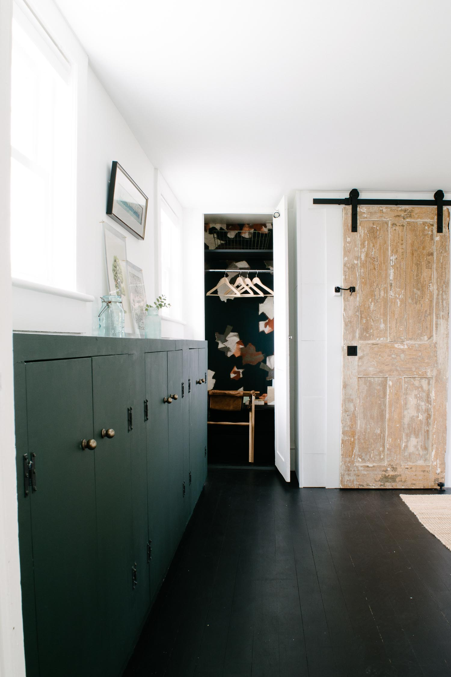 I loved this closet wallpaper, vintage sliding barn door, and painted black floors in this historic home. Designed by DIY & Home Bloggers This Giant Life.