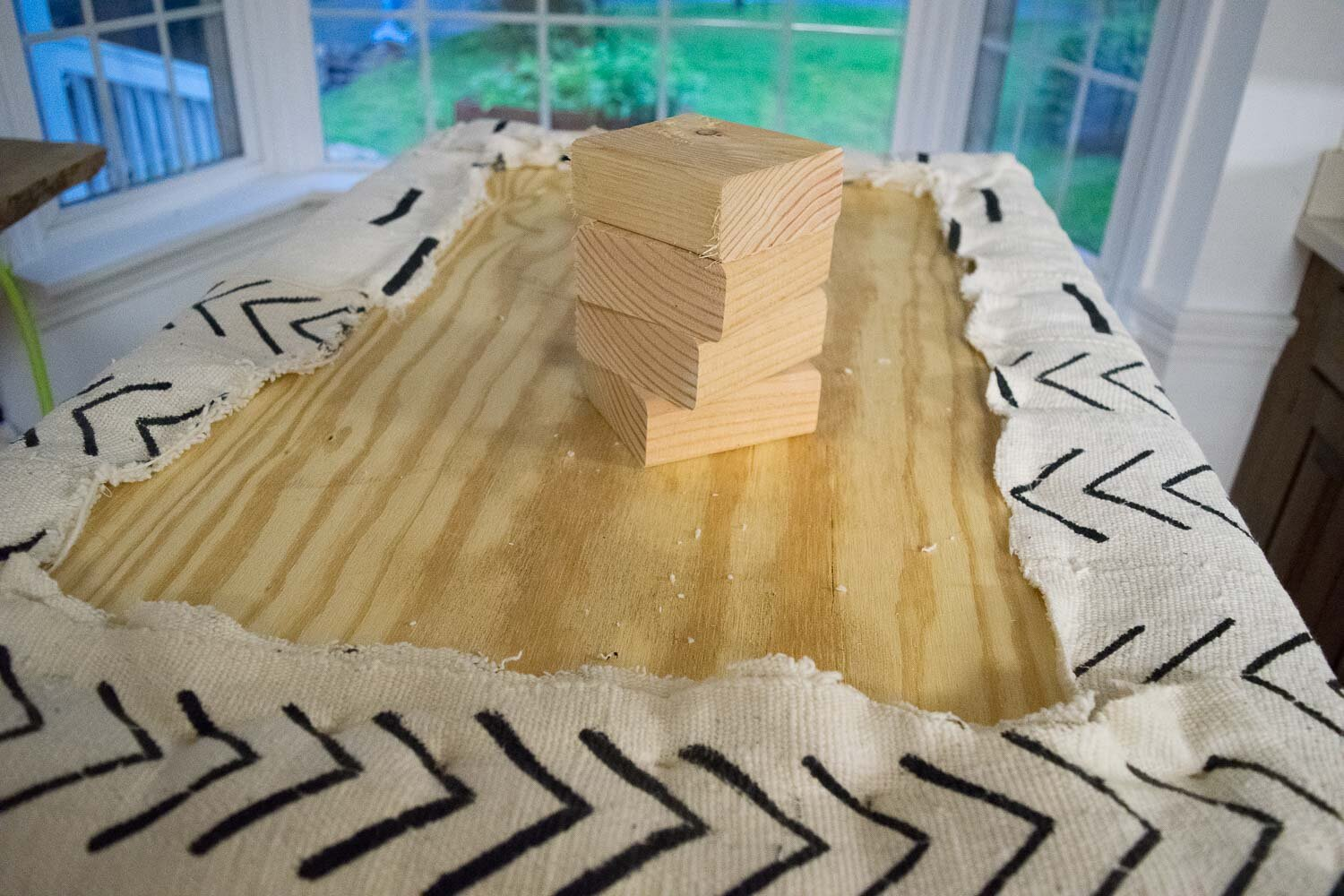 Stapling the Corners for a DIY Boho Mud Cloth Ottoman   Designed by This Giant Life