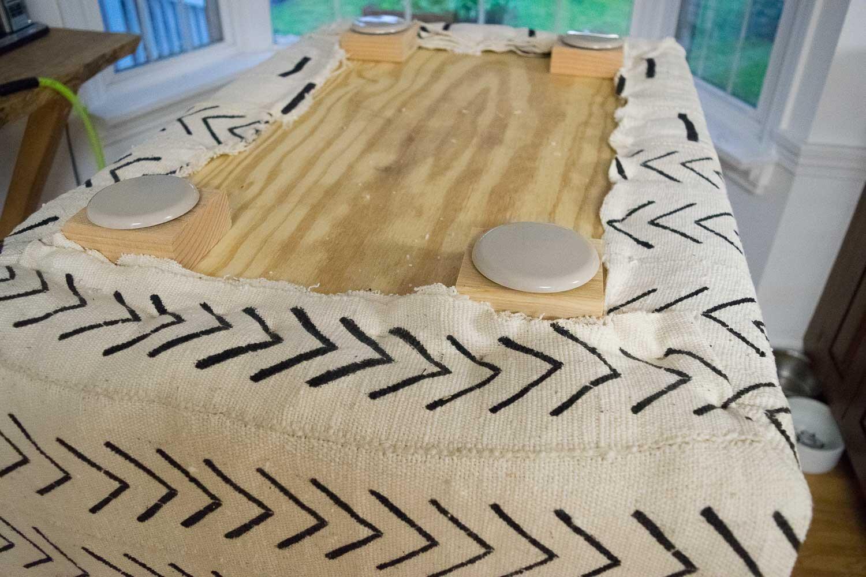 Adding feet to a DIY Boho Mud Cloth Ottoman   Designed by This Giant Life