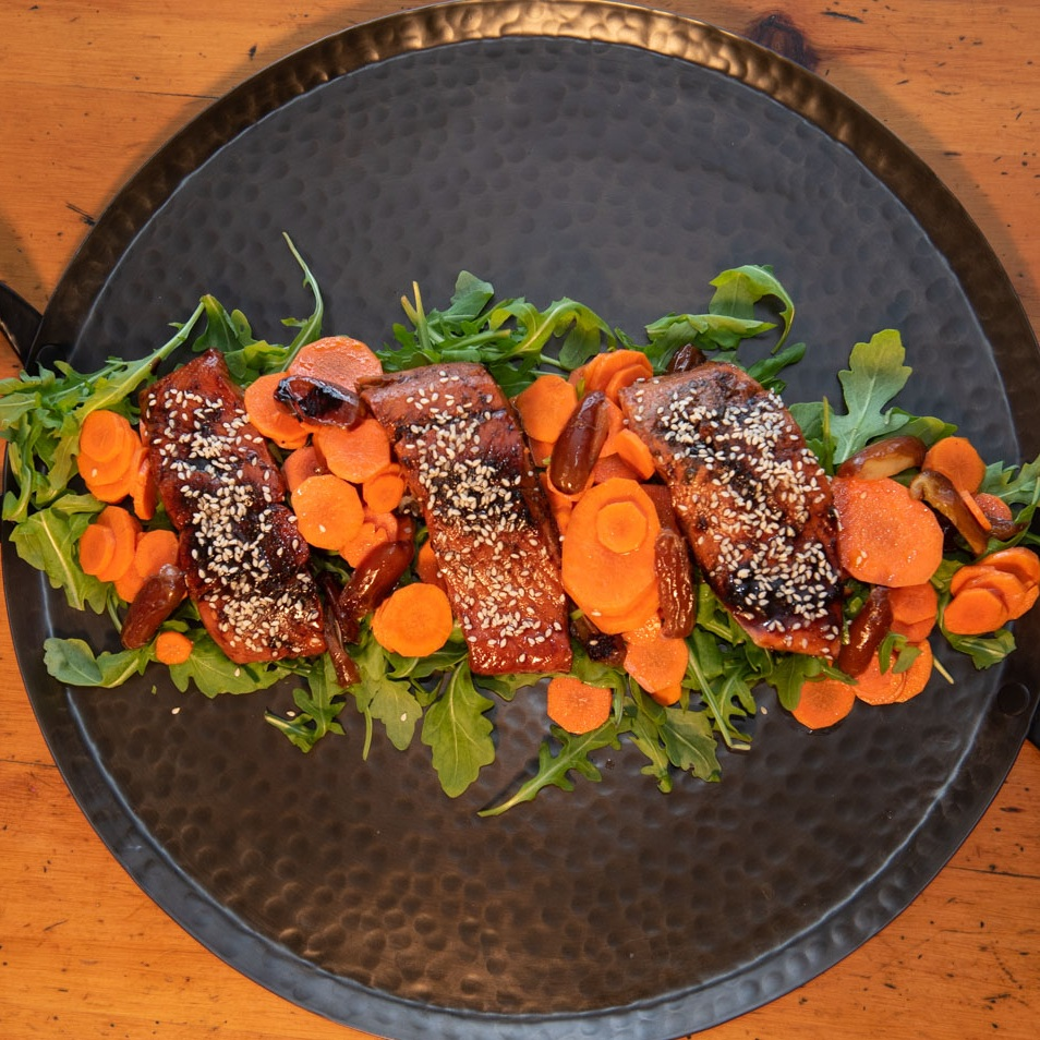 Vietnamese Caramel Salmon served arugula, shaved carrots and charred dates