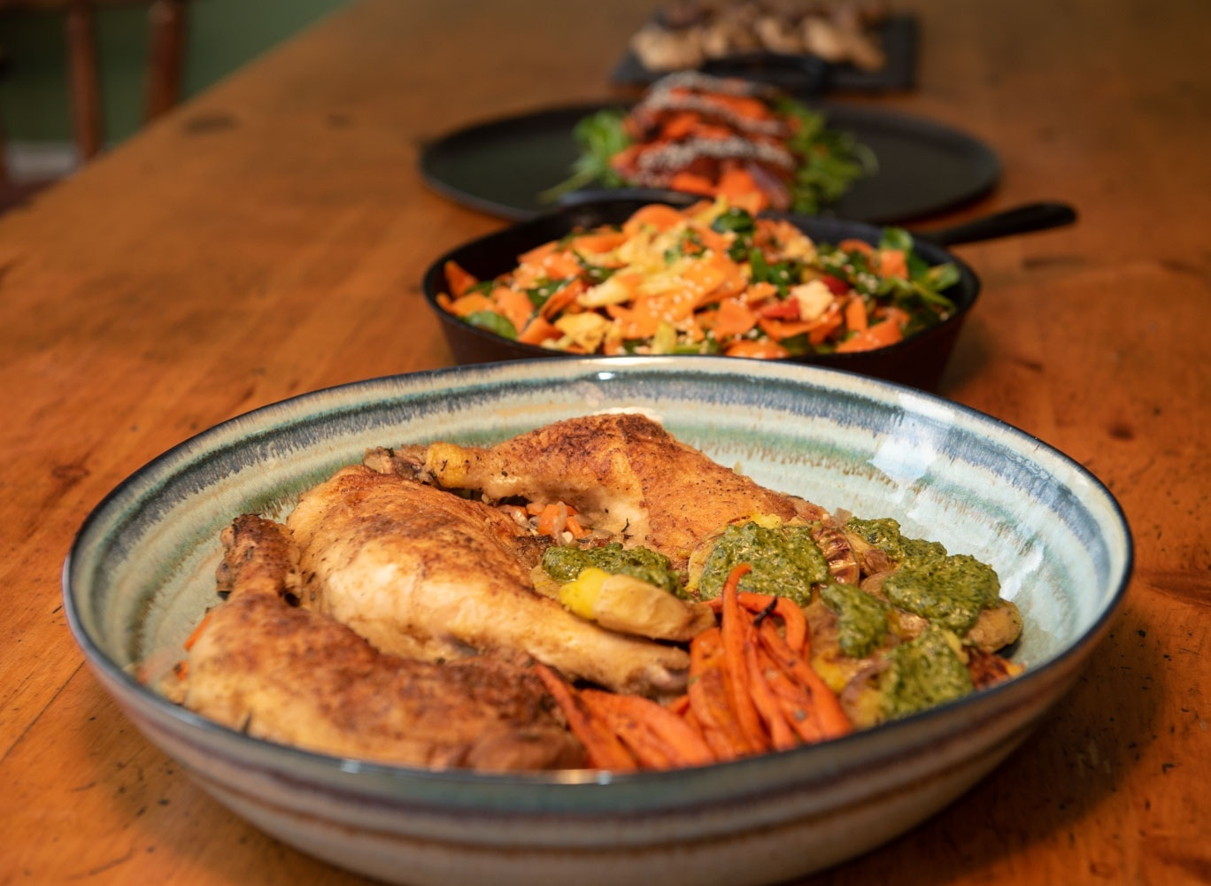 Braised chicken served with pesto-smothered crispy smashed potatoes and roasted carrots