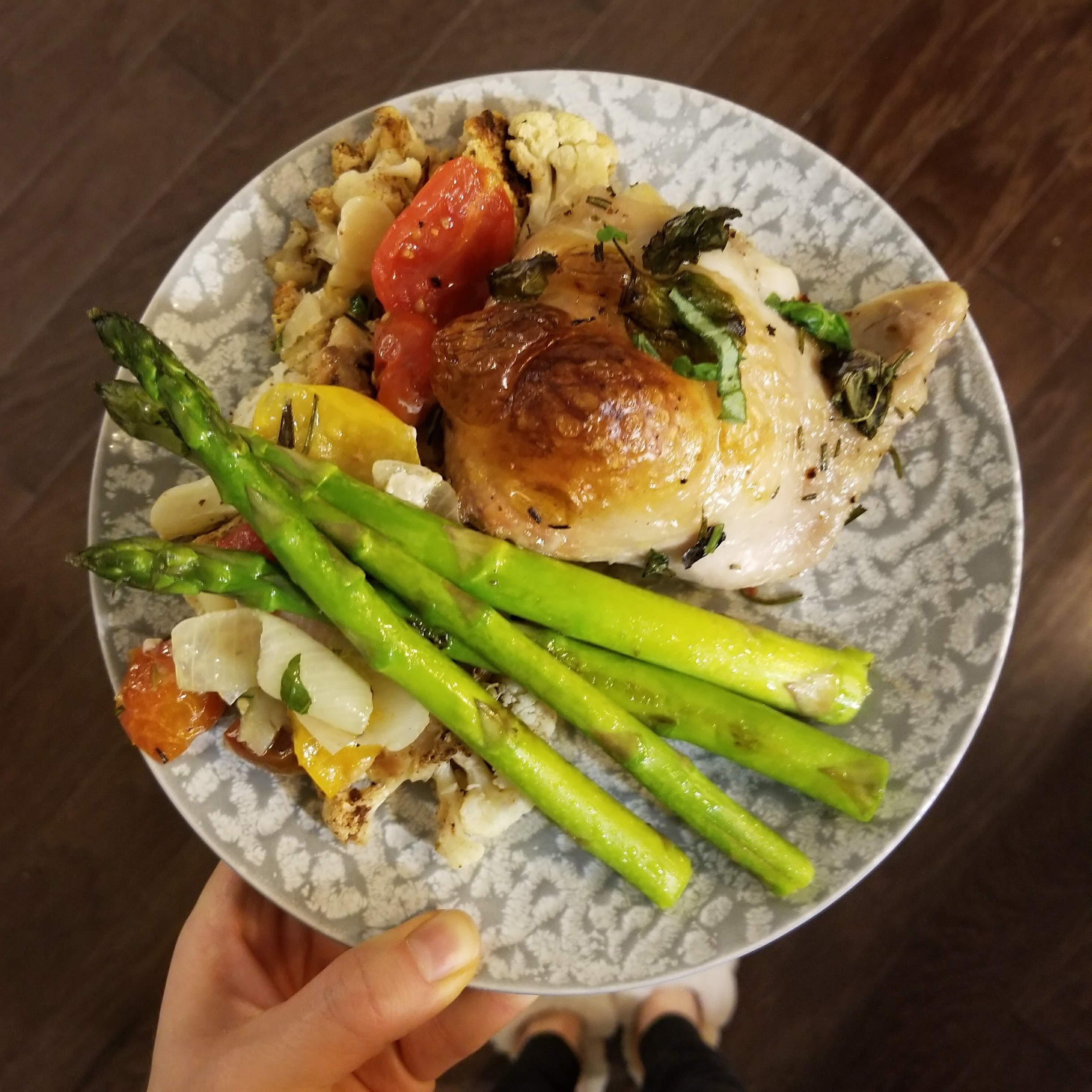 Crispy chicken baked with potatoes, tomatoes and herbs served with sauteed asparagus