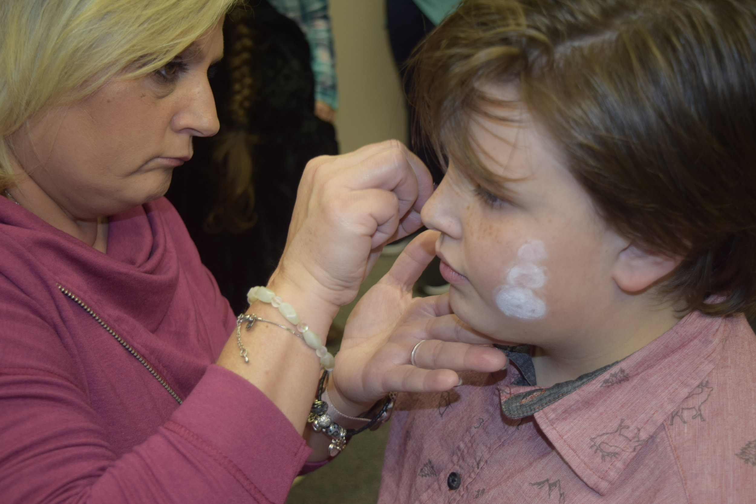 KJIF Project Manager, Jodie Lindsey, painting faces during a community Christmas celebration.