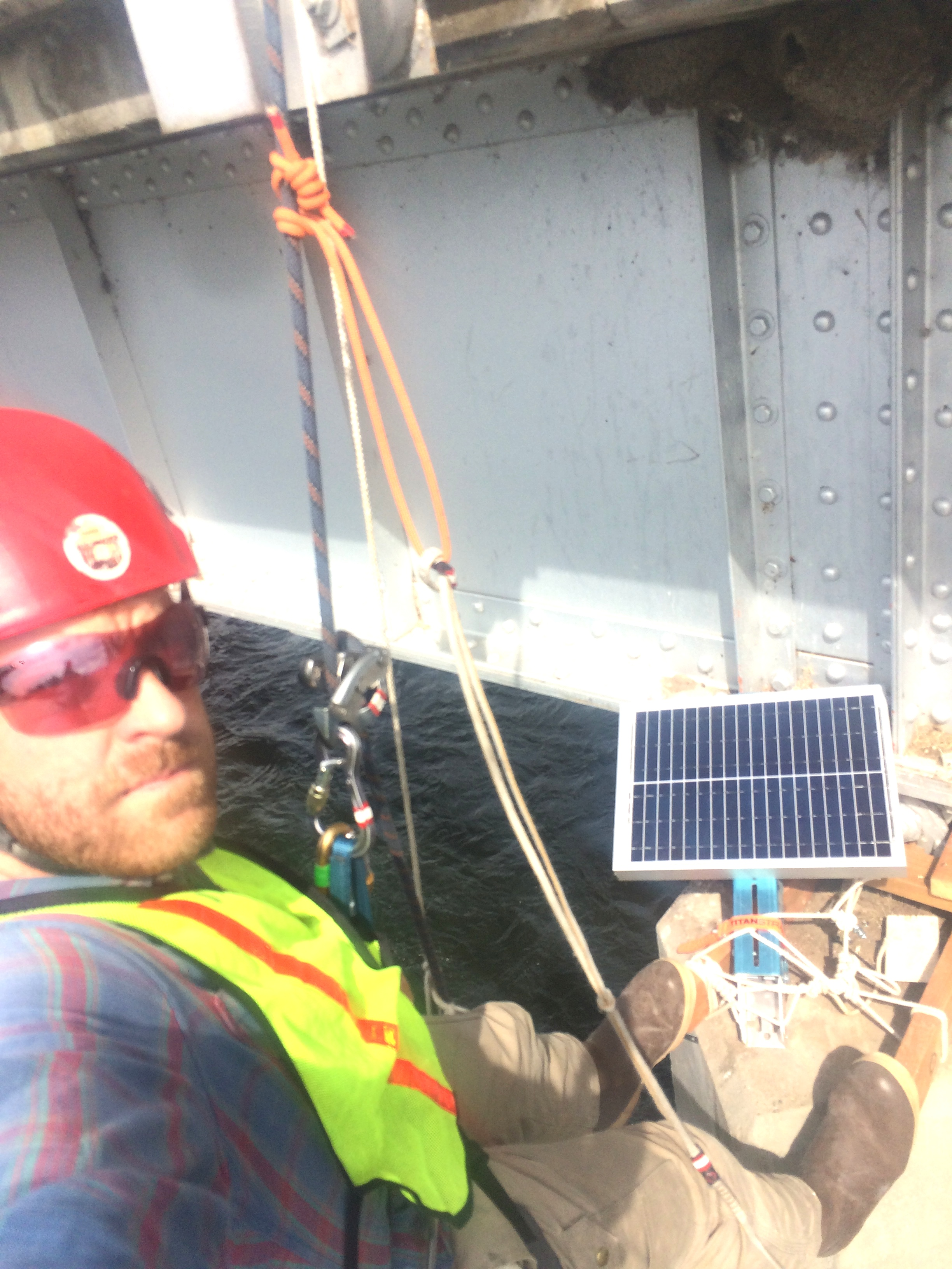 "Patrick working on the sensor's solar panel mounted on the bridge pier: the ""dirt"" under the panel is actually guano from the swallow nest above."