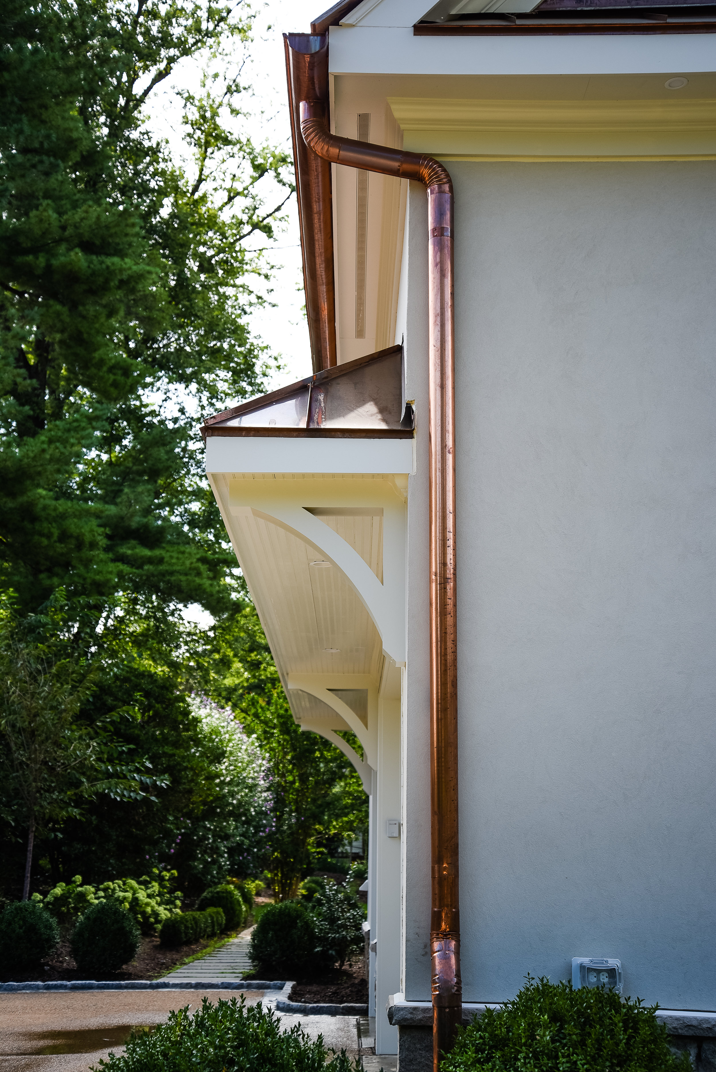 Round copper gutters &and downspouts with a creamy white stucco and custom-built overhang with corbels for garage entry.