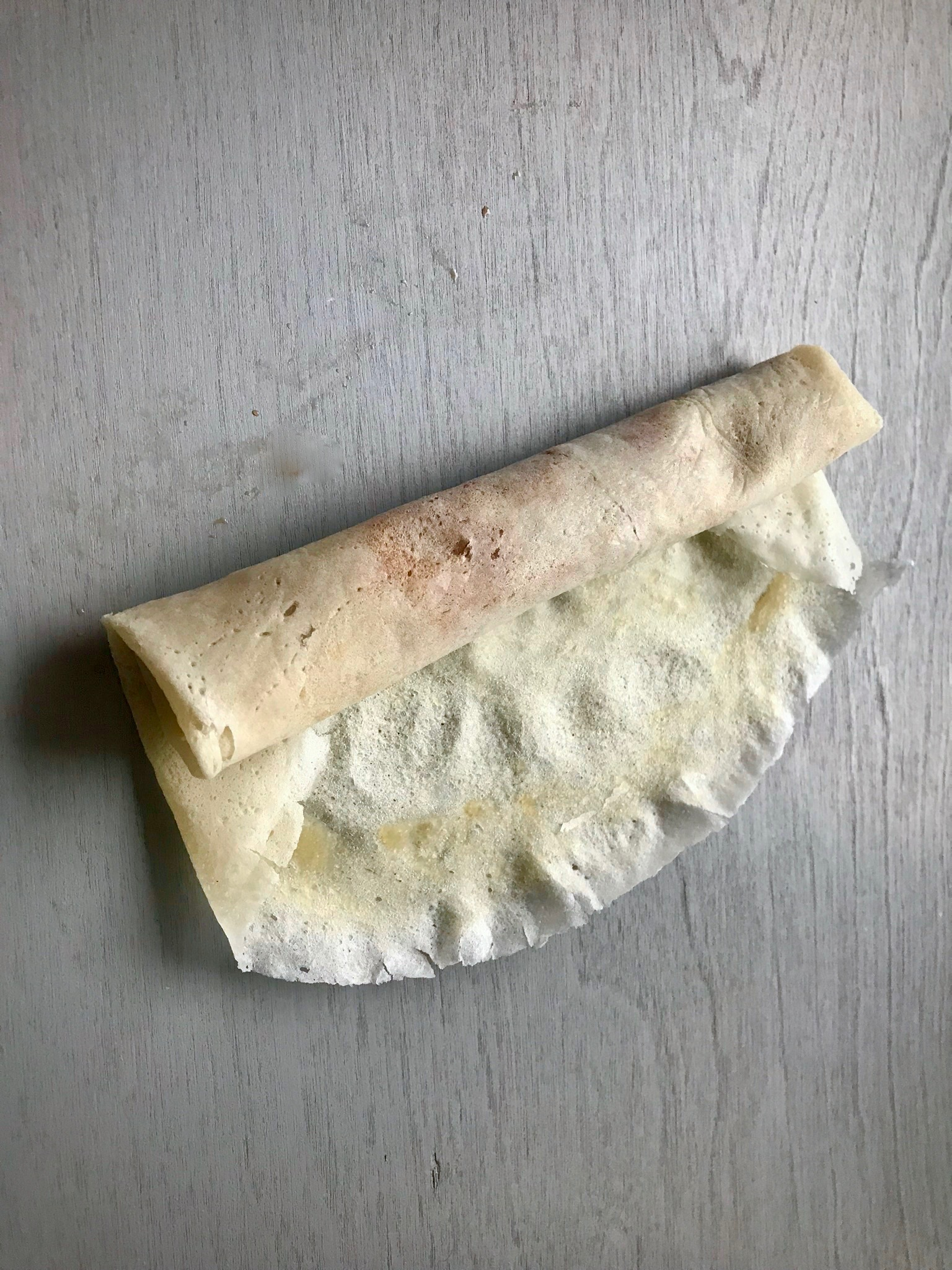 Finish rolling the lumpia and seal the closing edge with water