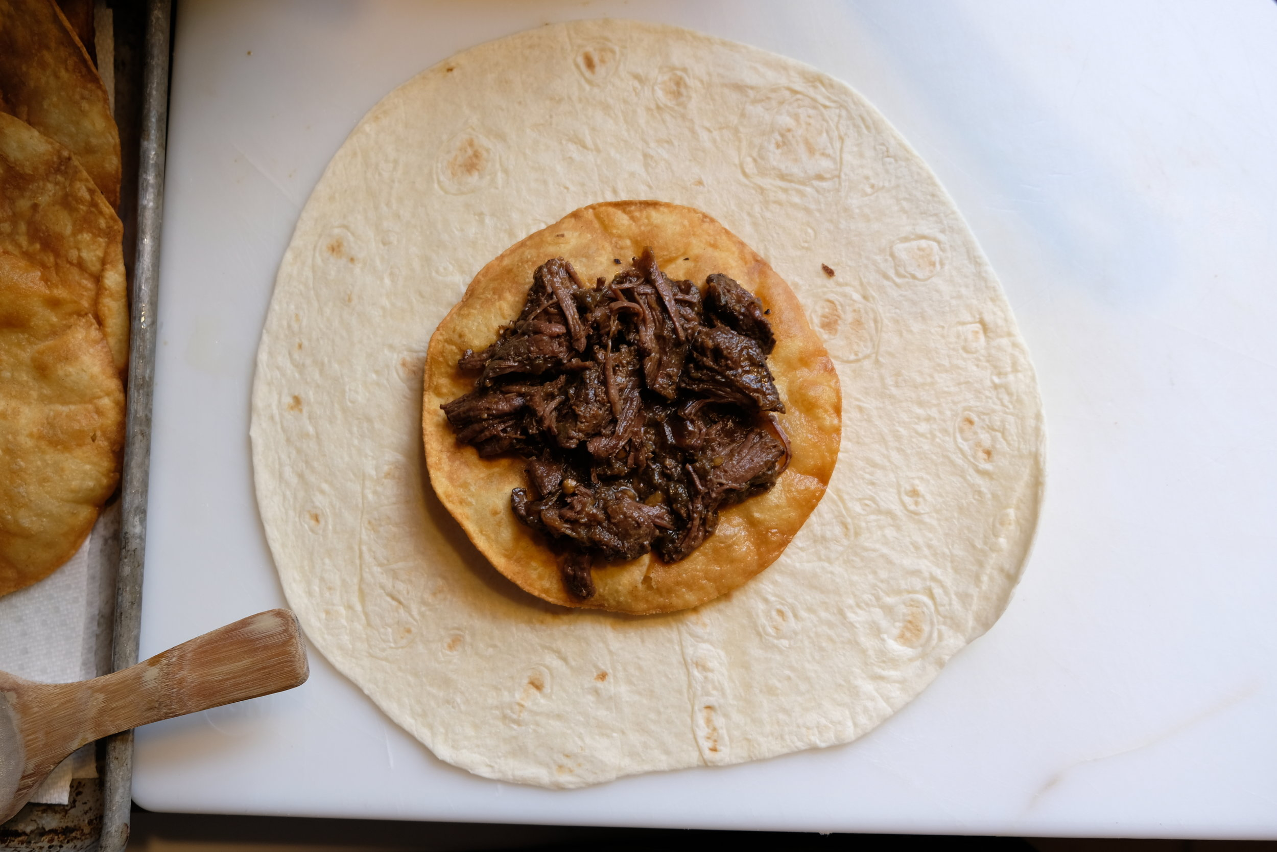 Center the corn tortilla over the scoop of refried beans, and top with meat