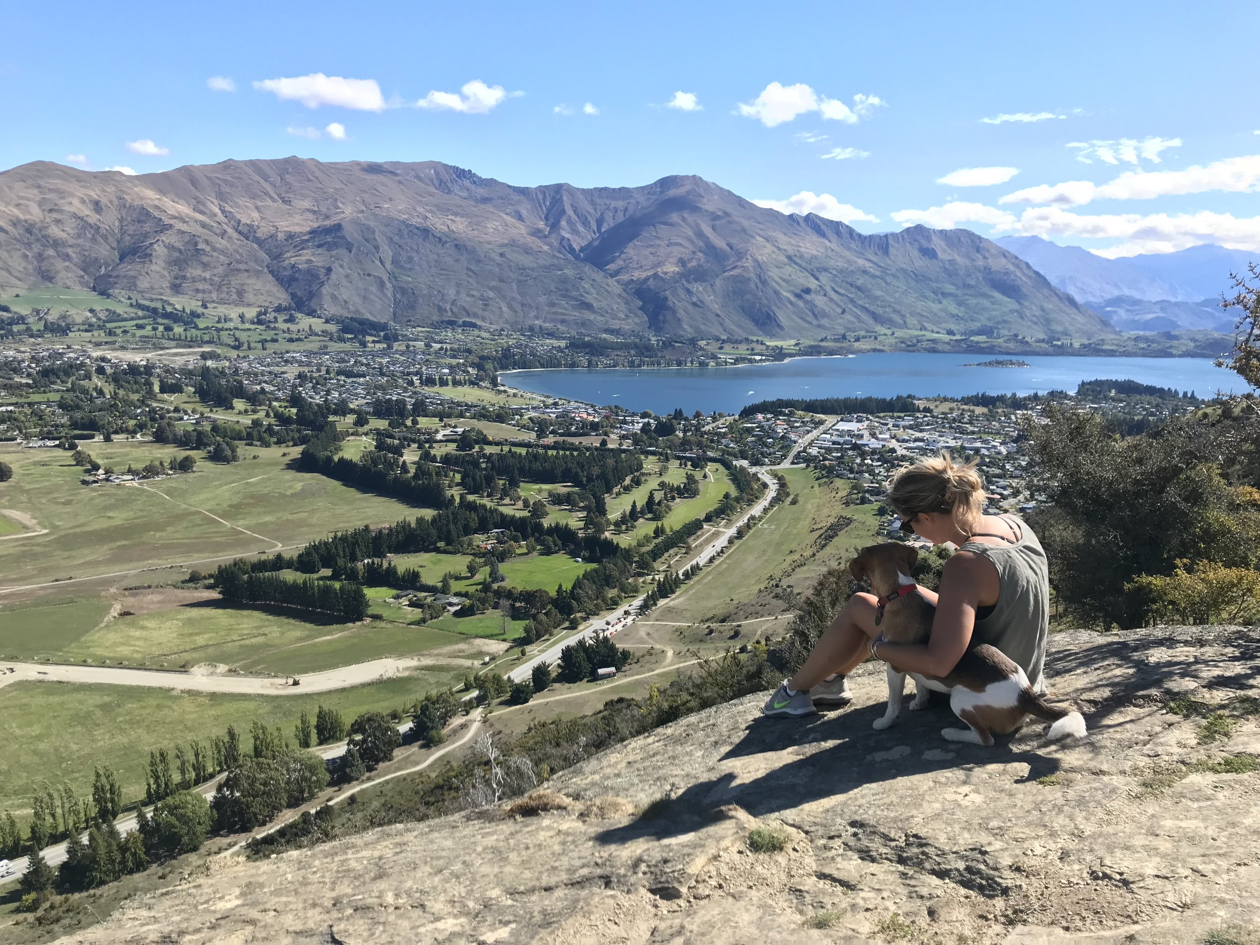 Wanaka is the place I feel most at home. It is a small, but increasingly popular, town in the South Island of New Zealand. My family has lived there for four generations. This photo was taken from the top of the Mount Iron track, and is of my cousin and her dog. I love doing this walk when I first arrive back because I'm reminded of old memories on Lake Wanaka and can also see new developments in the town.  Isabel Donaldson