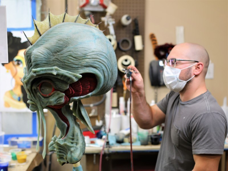 An artist applies finishing touches to an Animax character