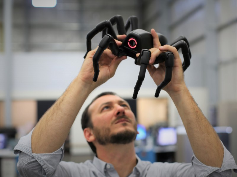 Director of R&D Rob Gosnell studies a robotic spider