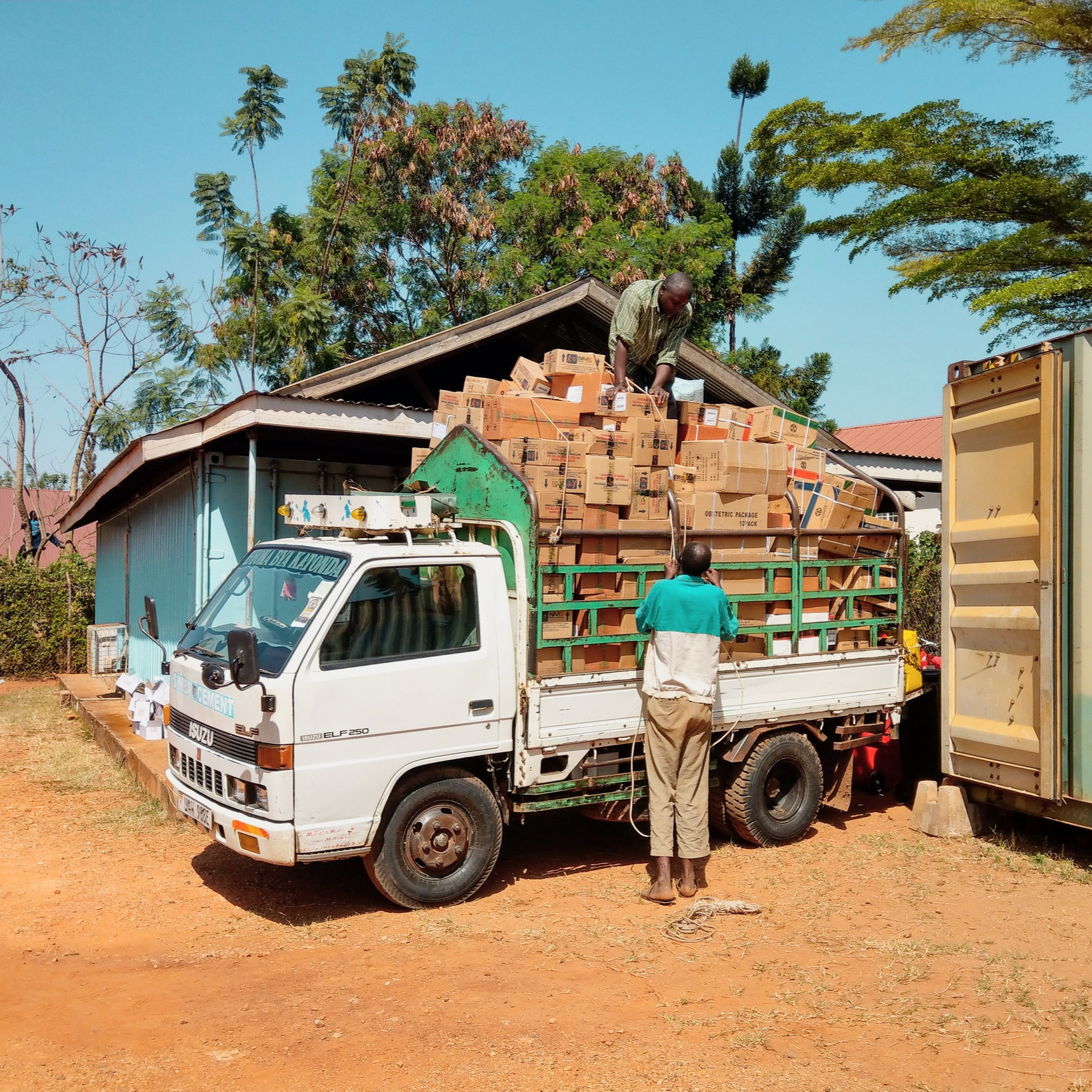 The truck is being loaded with medical supplies for delivery within the Mbale Health District.