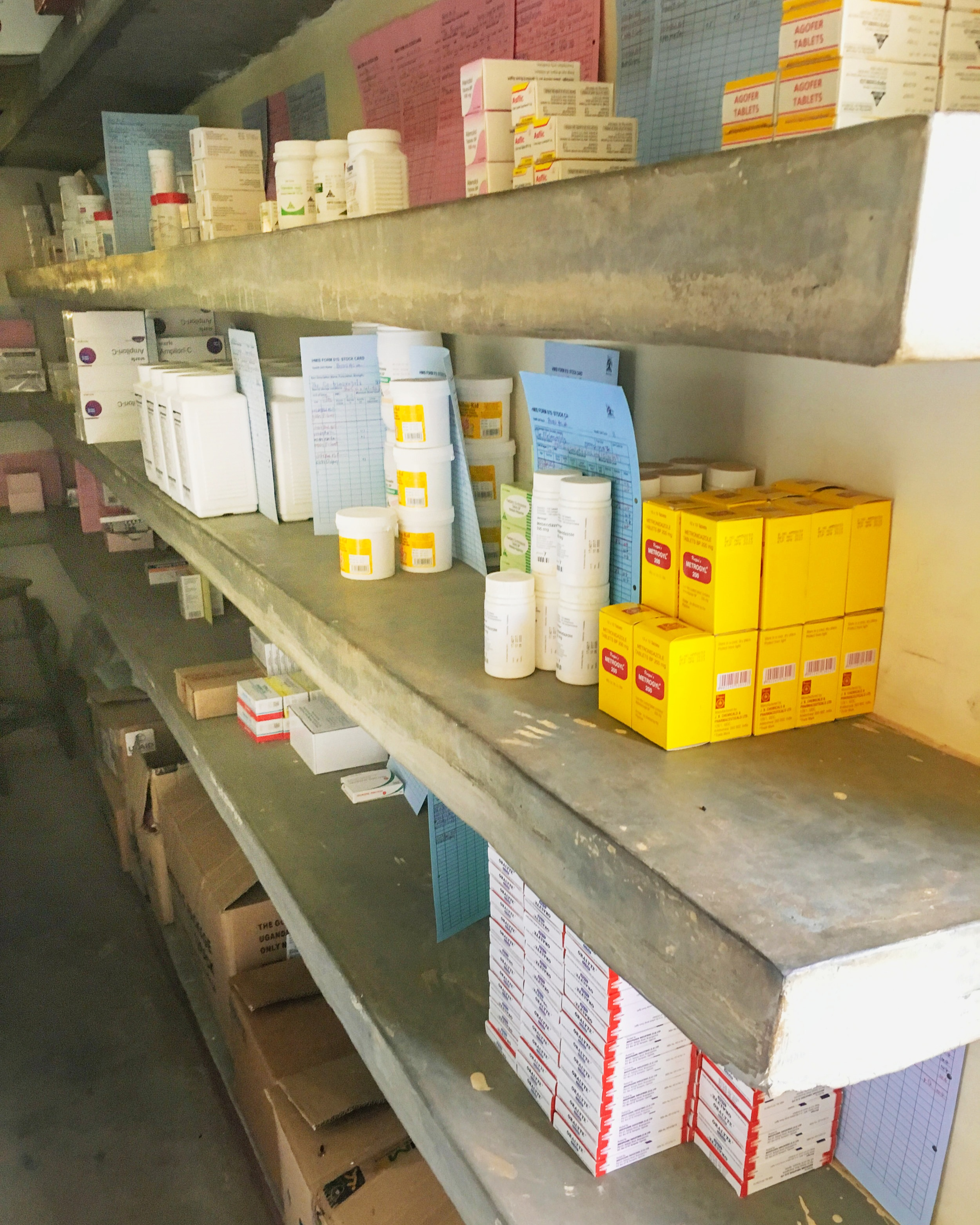 """That means immediate knowledge, prompt solutions, swift interventions and better planning. - Left: A typical Medicines Store at a Health Centre. Each inventory item is placed next to a paper """"stock card"""" which must be updated to track its consumption."""