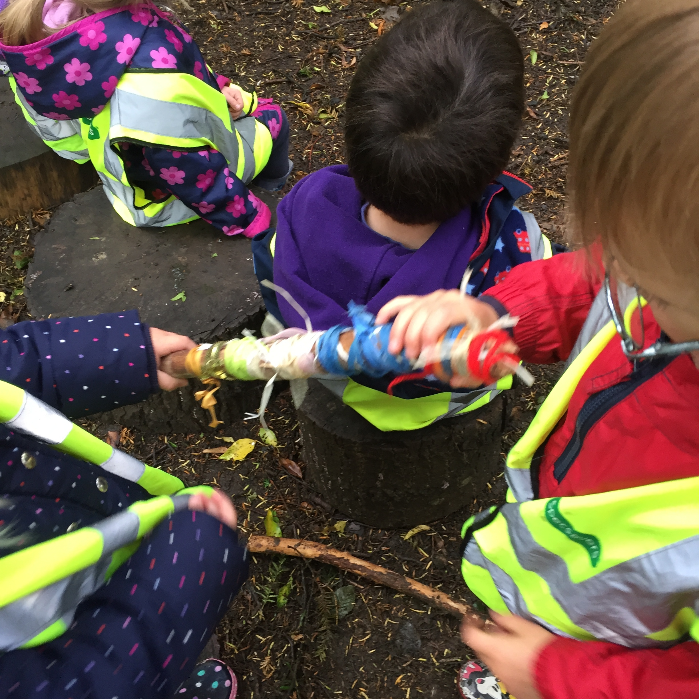 Th children pass the fire stick to learn about being safe around fire, staying 'outside' of the area.