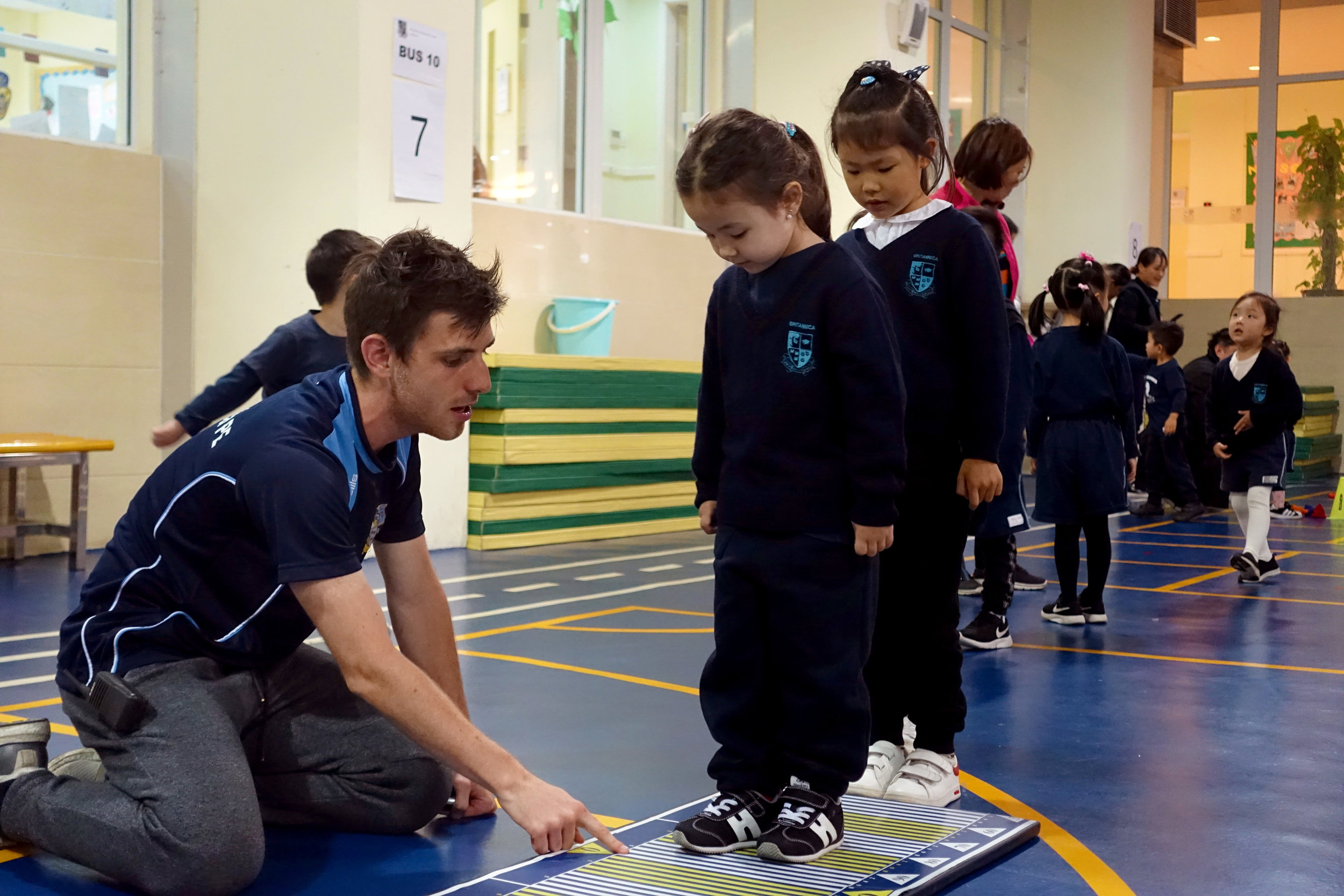 Teaching nursery students how to do their first standing long jumps.
