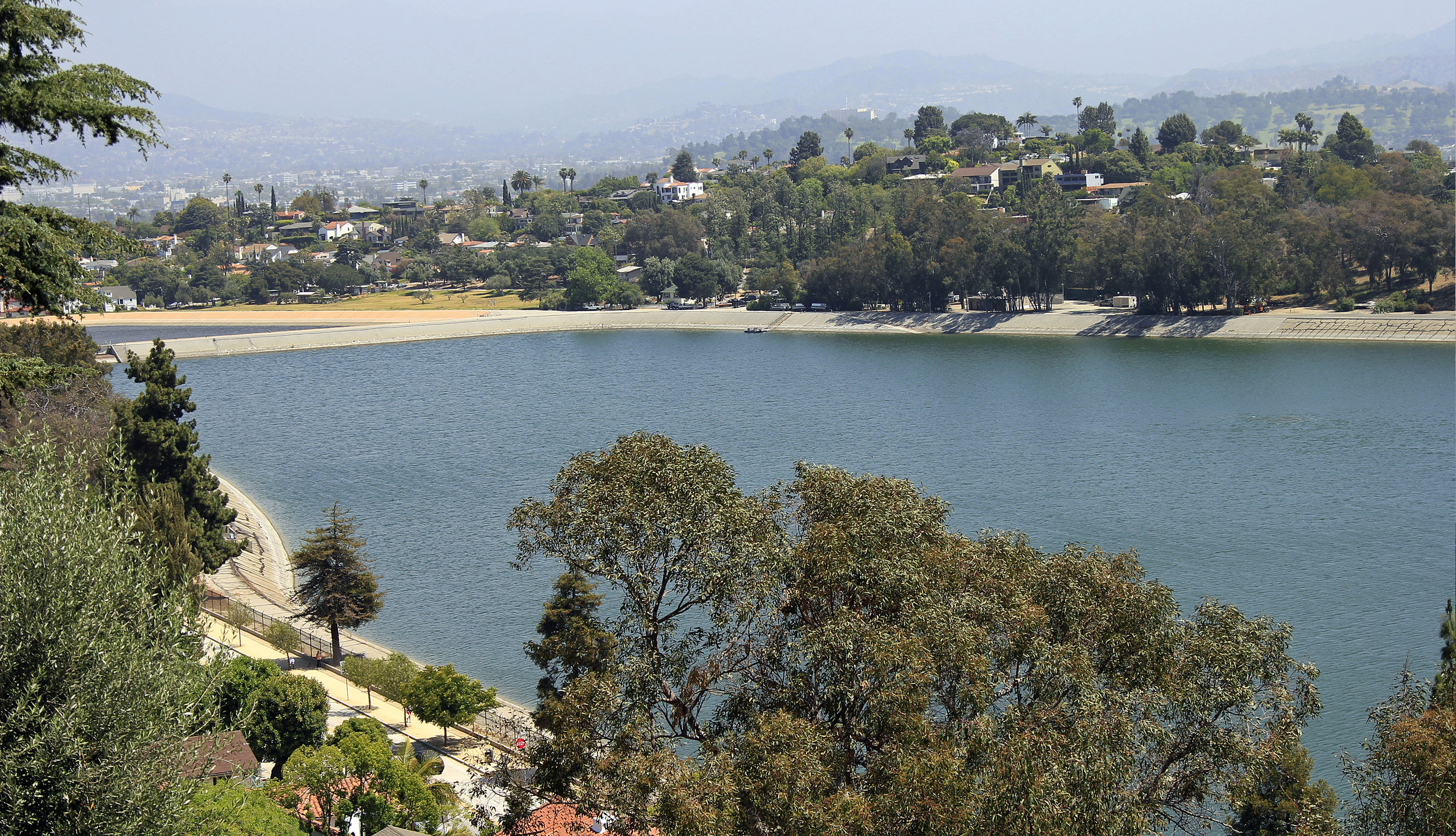 The shimmering reflection of the Silver Lake Reservoir and its hilly, surrounding neighborhood. The Angeles National Forest in the San Gabriel Mountain range is seen in the distance.   Learn more about Silver Lake...