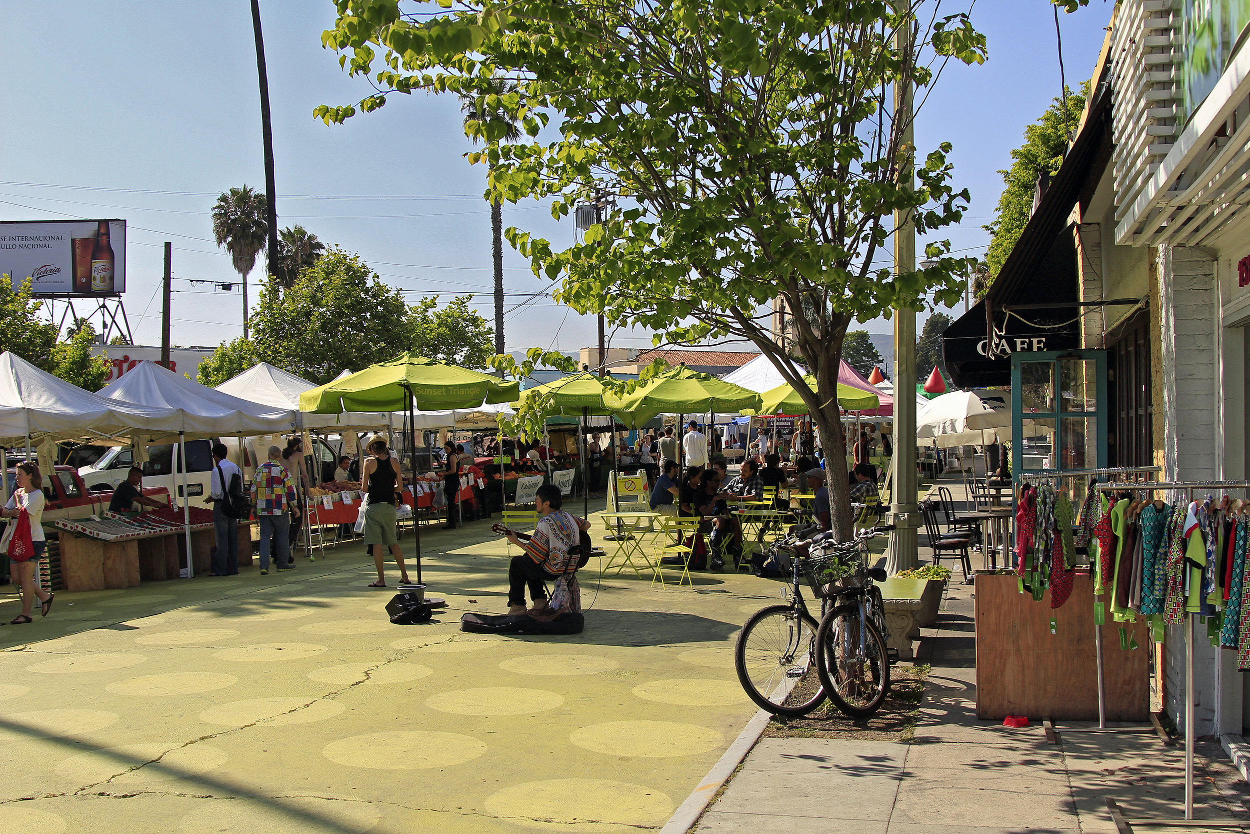 A street performer and vendors at Silver Lake farmers market at Sunset Triangle Park along Sunset Boulevard.   Learn more about Silver Lake...