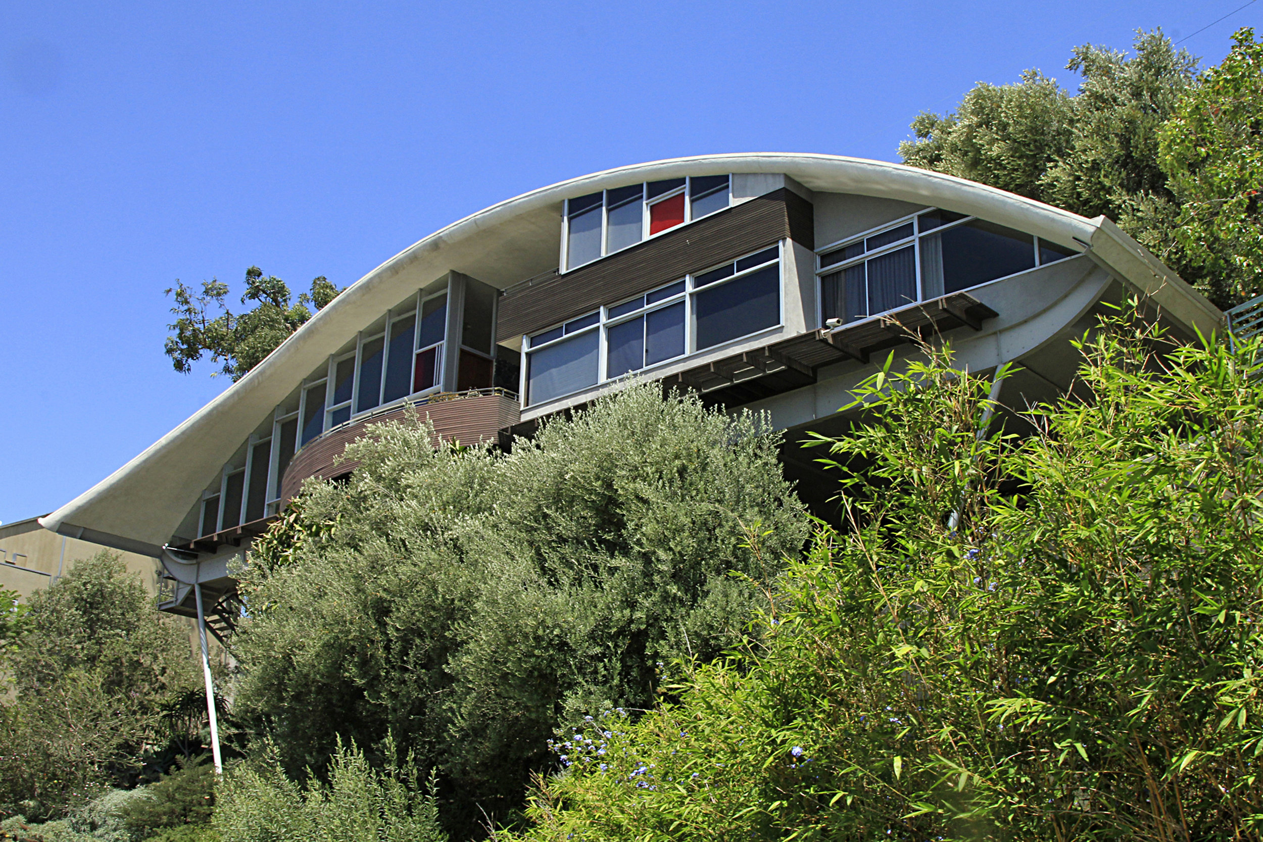 "Garcia Residence - John Lautner. 1962. Hollywood Hills, Los Angeles. The 2400 square foot home, with its sweeping roof and scattered panes of pink, red, and green glass is also known as the ""Rainbow"" House.    Read more about the Garcia Residence...."