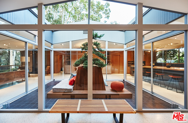 Upon entering, you are confronted by a large and striking glass-enclosed atrium, which contains a specimen Japanese cedar surrounded by a beautiful wood platform for lounging. This is a very special touch in the home's design and would almost certainly be a conversation starter for anyone's initial visit to the house.