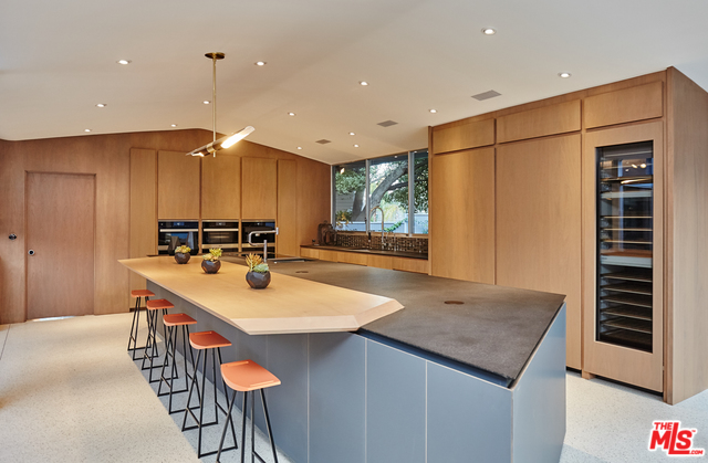 My favorite thing about the kitchen is the massive island with its cantilevered slab of wood that serves as the eating area. Clever and chic, indeed.