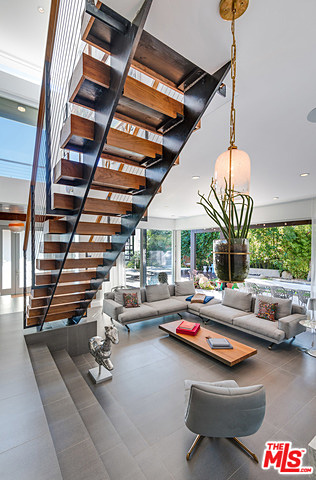 The aforementioned floating staircase and family room beyond it, whose entire south-facing wall has been modified to feature floor-to-ceiling sliders that open to the lush and private yard with heated swimming pool.