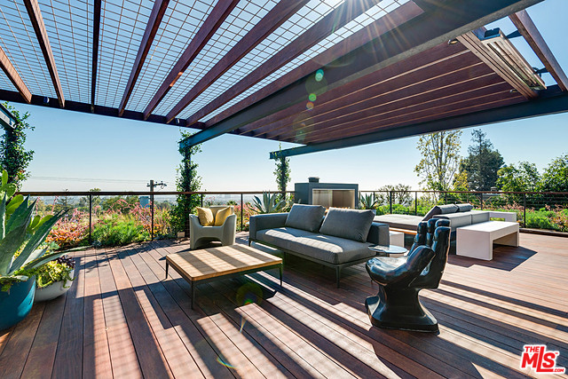 """There are decks on two levels made from mangaris wood and the upper one features a succulent garden wrapping around its perimeter, an Ecosmart fireplace, a 65"""" all-weather Sunbright TV, built-in heaters, fridge/sink, ice maker and perhaps my favorite feature…"""