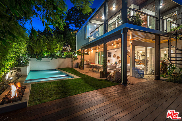 The yard is a verdant oasis featuring a pool whose water is warmed by a gas heater, a waterfall, Boffi outdoor shower, Bega landscape lighting, and fruit trees.