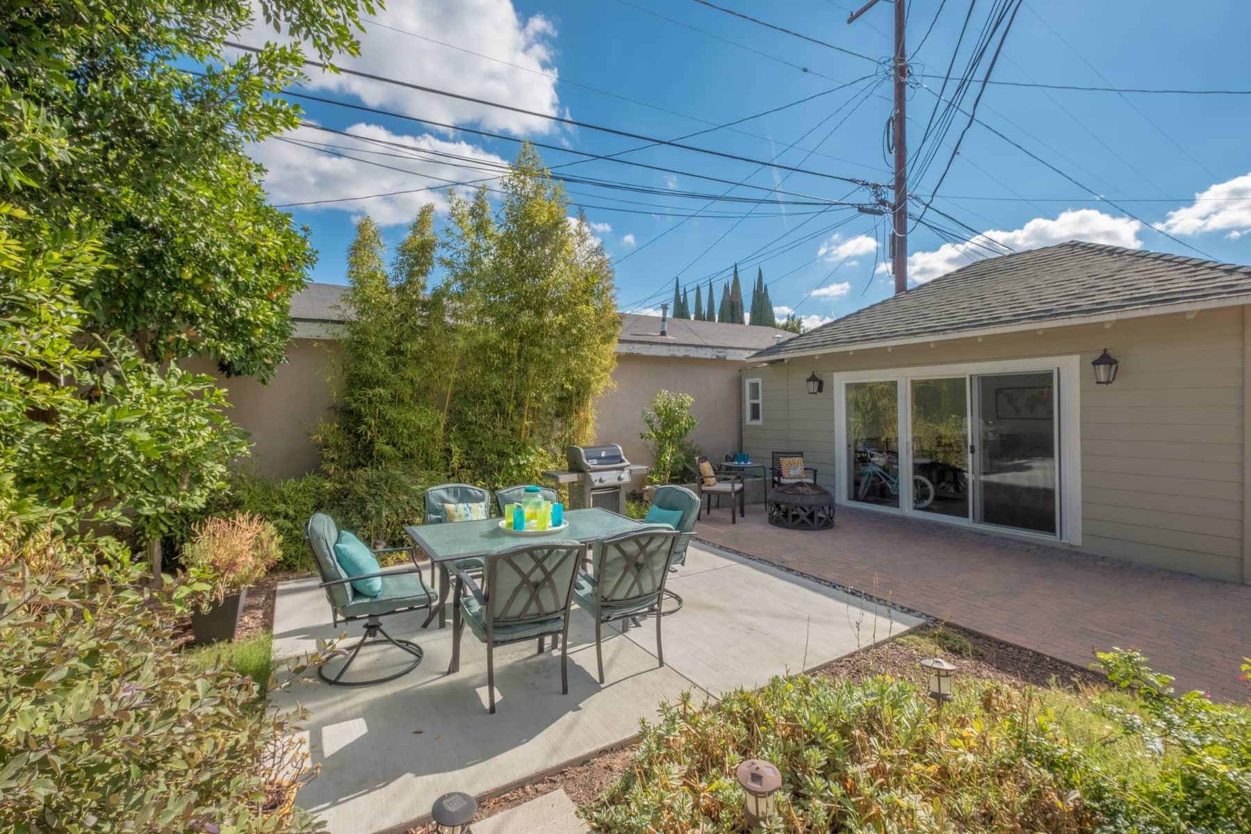 There is enough parking space to accommodate 6+ cars along the long brick-paved driveway, which is divided in half by a motorized security gate. And in the back, a private yard features lots of patio space surrounded by gardens and fruit trees.