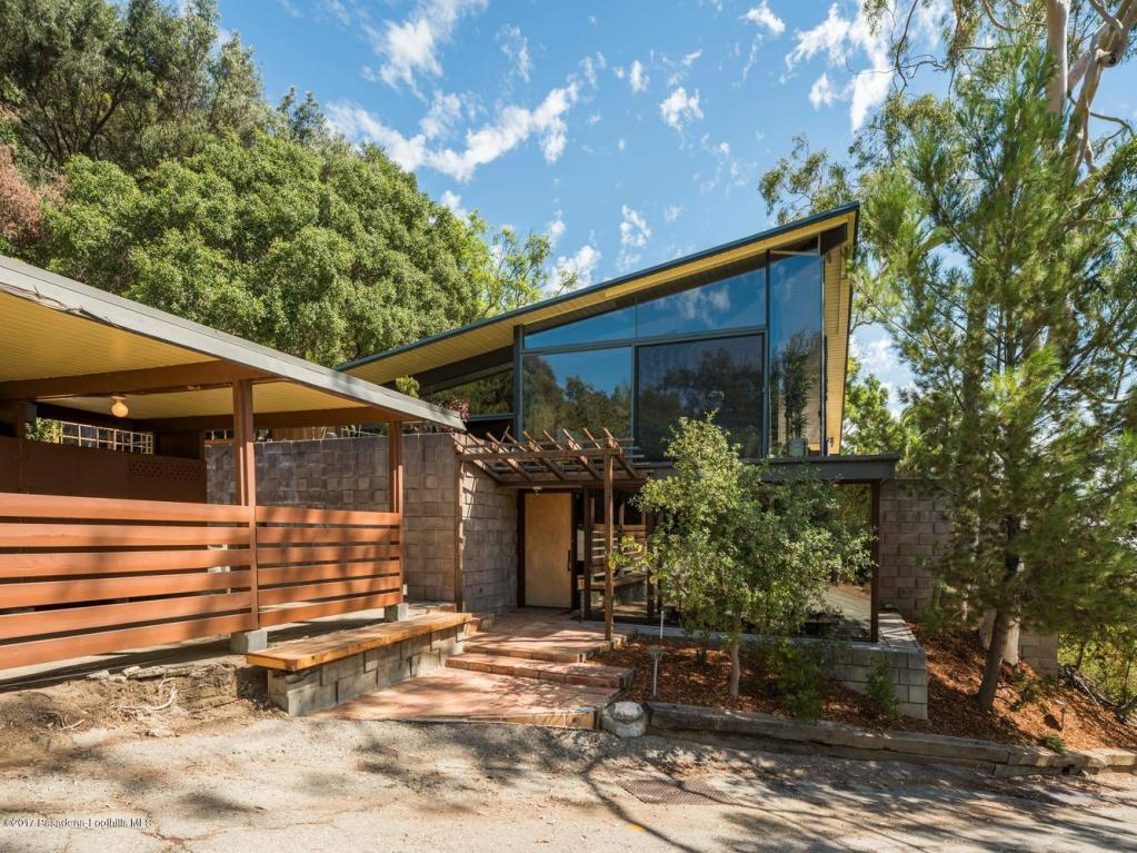What I find particularly compelling about this home is that while it has very distinct mid-century post and beam elements, it also manages to capture a rustic, cabin aesthetic, which is beautifully complemented by a 22,000 square foot parcel with mature trees that surround the house.