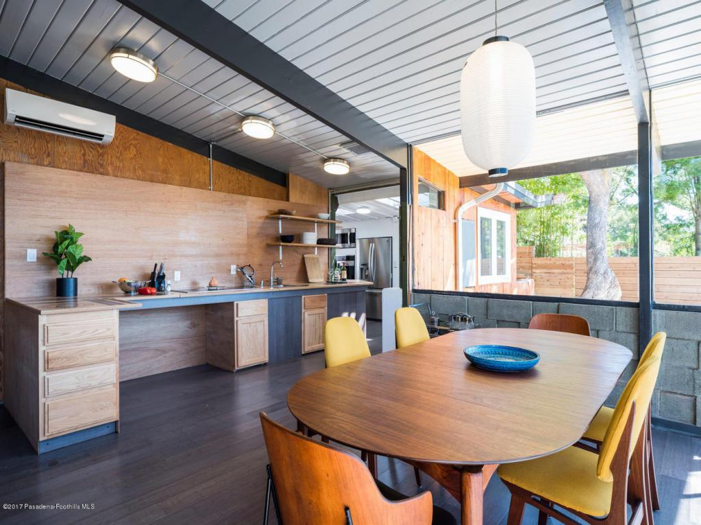 Open concept is the theme here, where the living room continues into the dining room, which merges into the kitchen, with high open beam ceilings lined with tongue and groove wood throughout.