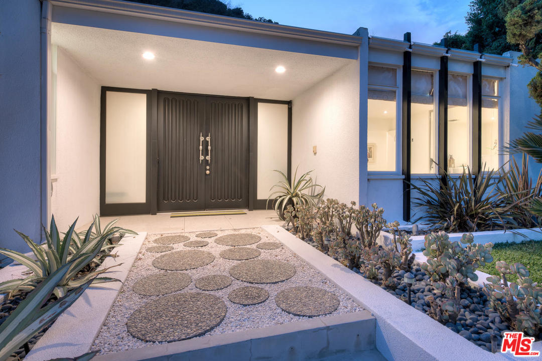 If I were blindfolded and led to this entry, I would immediately guess Benton & Park. The large, floor to ceiling doors, flanked by frosted glass and a deep overhang all have their thumbprints on the design. And the very mod stone pavers provide the perfect accent to this entry.