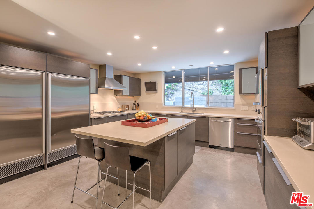 Back inside, the kitchen has been very tastefully updated for today's living. It features custom Pedini cabinetry, quartz counters and center island.