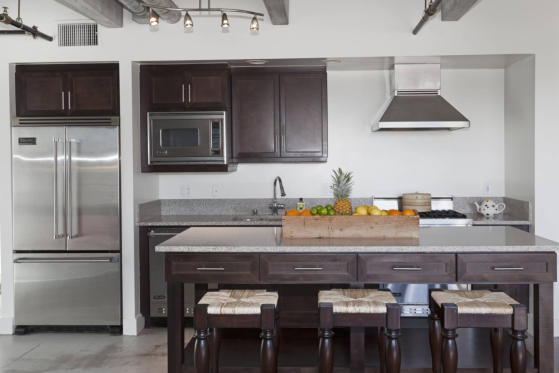 The kitchen boasts all Viking appliances and a huge island, featuring with a granite top that matches the counters along the sink and cooking area. And because this island is on wheels, you can esily move it around to reconfigure your space as needed.