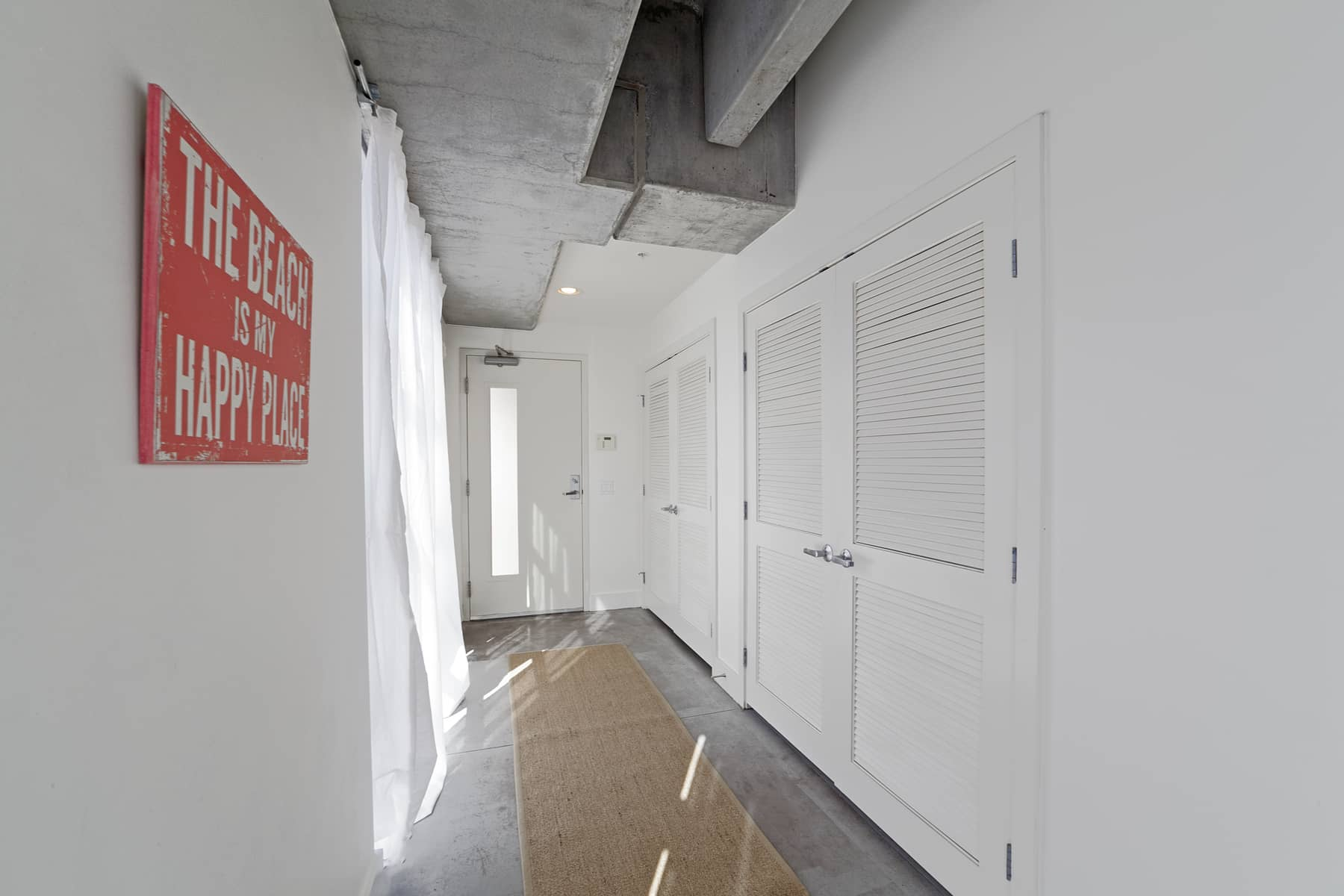 The long entry has a wall of windows along one side, and, along the other, a large coat/utility closet as well as a washer/dryer area.