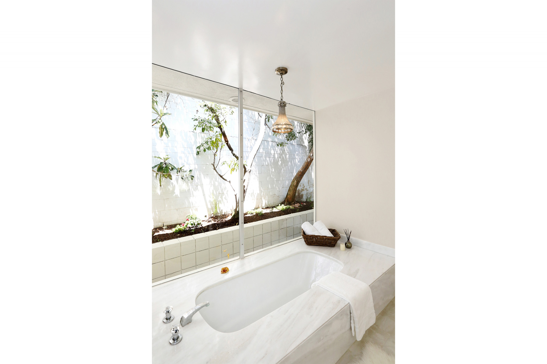 The tub, which appears small thanks to the massive marble box that surrounds it, is actually quite long. With a giant picture window beside it and a mini-chandelier overhead, this is clearly intended for prolonged luxuriating. The room also features a separate shower and private toilet stall.