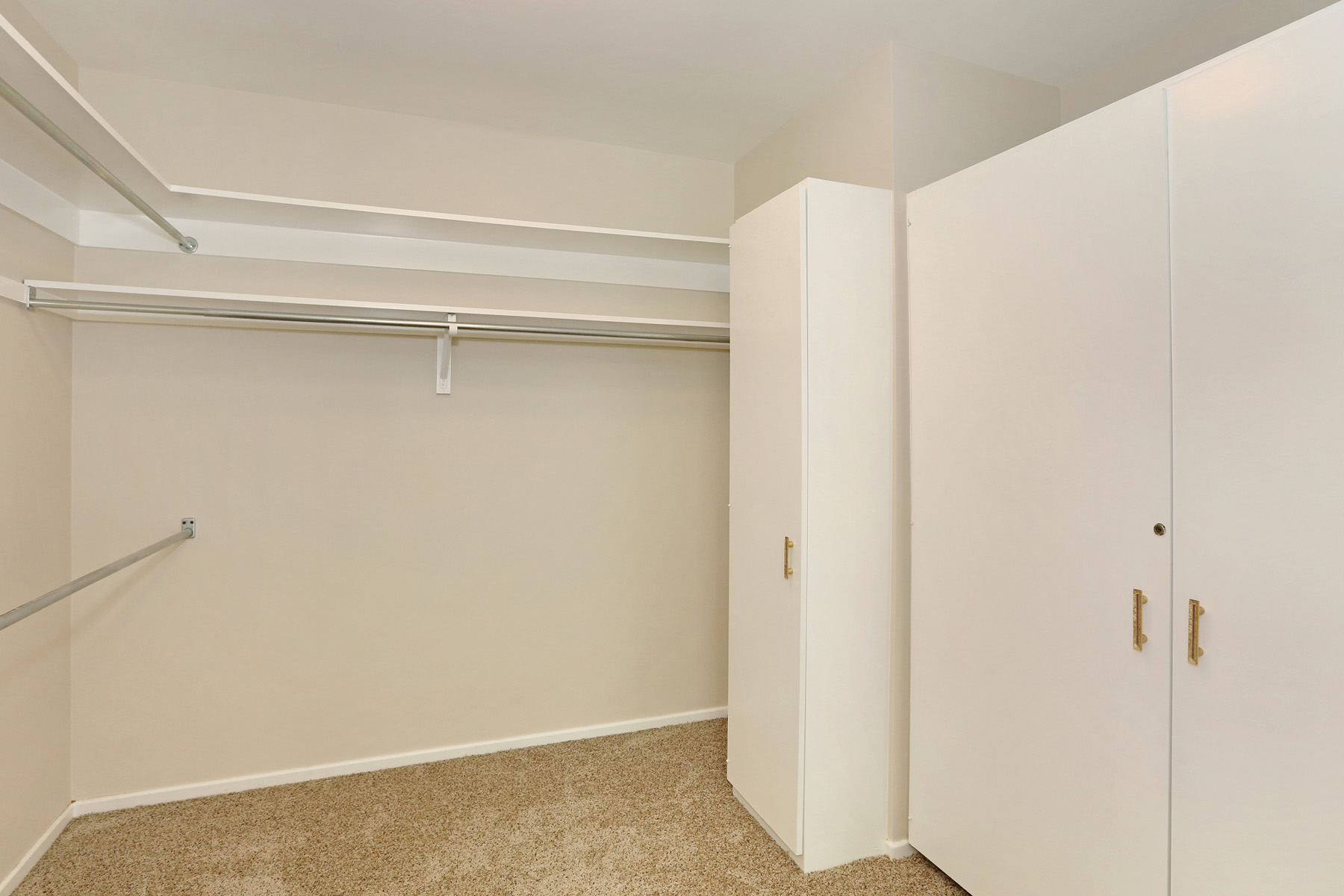 This walk-in closet has a wall of built-ins, including a cabinet just for shoes.