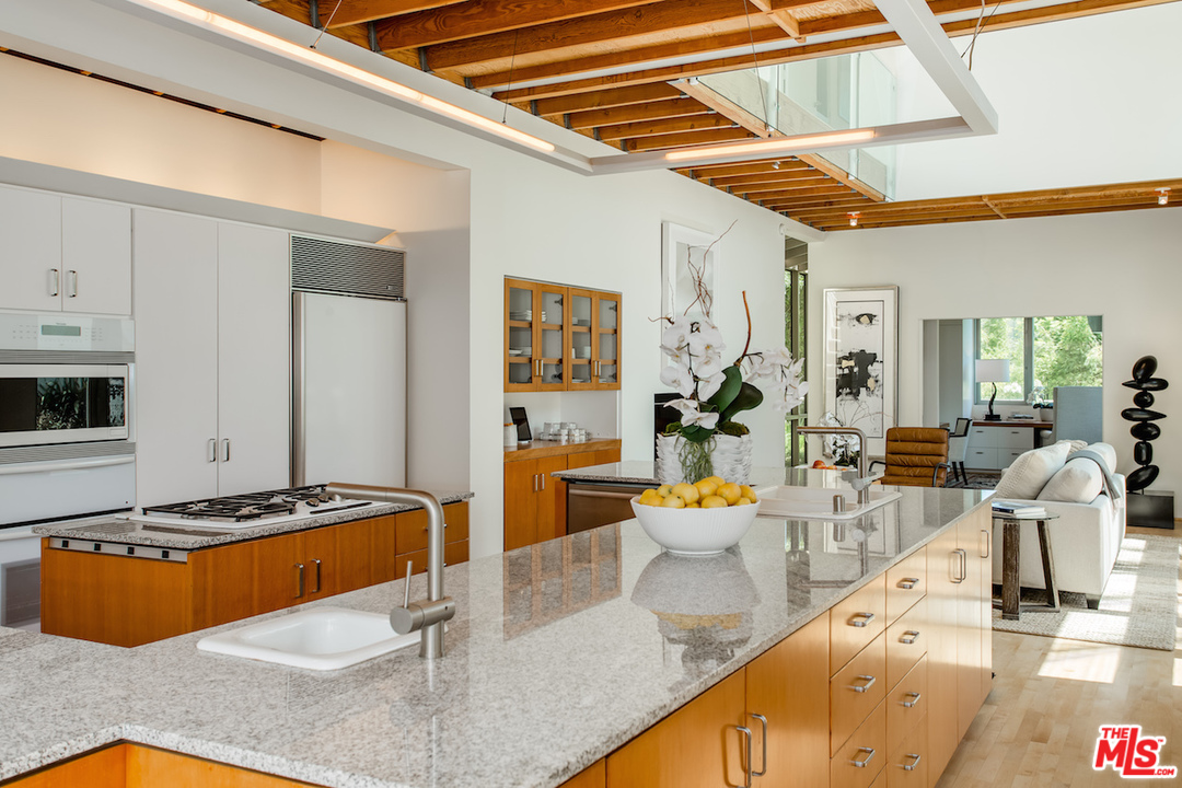 The kitchen is a long, sprawling workspace whose finishes are in keeping with the rest of the house. As with most every room in the house, it's flooded with natural light and opens up to the yard.