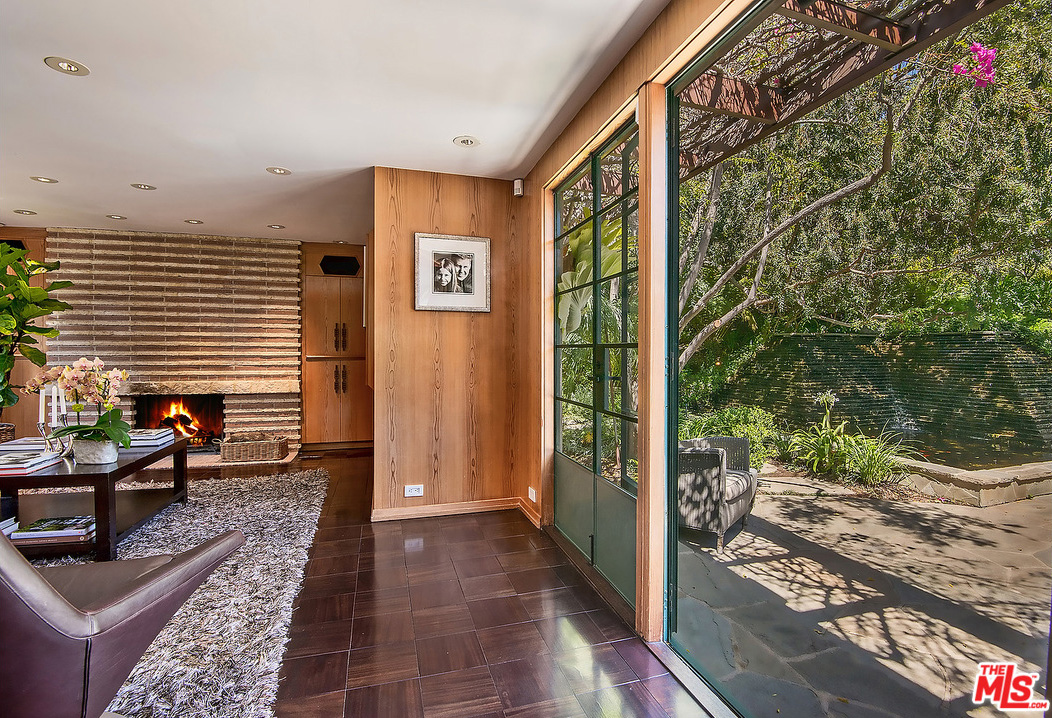 Outside, a luxurious patio featuring slate flagstone can be accessed from both the living room and the den via those gorgeous steel-framed-window doors.