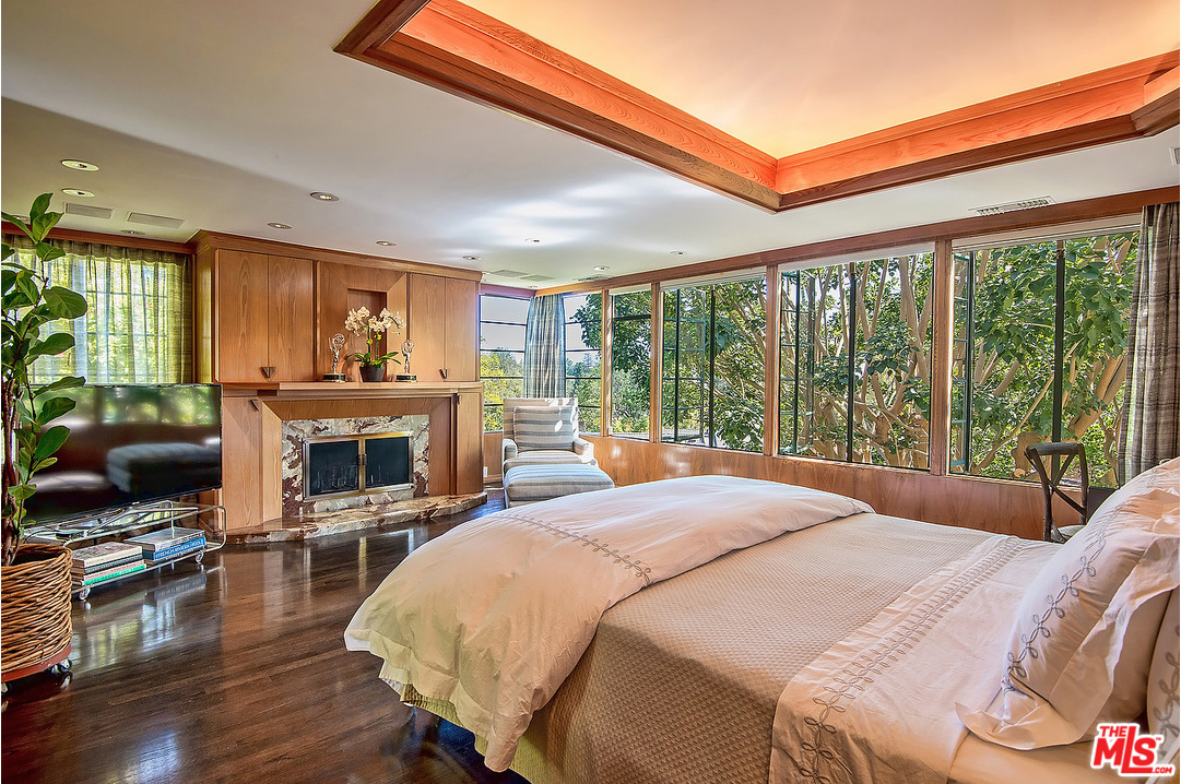 The master bedroom is designed with windows on three walls, bringing in loads of light and peaceful views of the surrounding greenery. Matching the design of the living room and dining room, a large area of the ceiling above the bed features the same recessed design with built-in lighting.