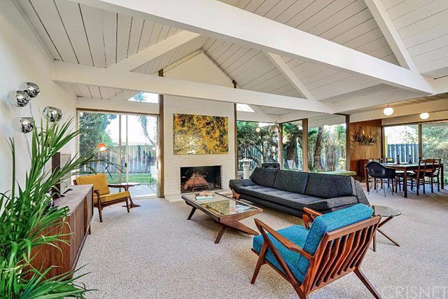 Inside, the home enjoys a design with an open floor plan and walls of glass that lead to the courtyard, as well as the backyard. The bright and airy living room feels quite spacious thanks to high ceilings composed of exposed beams and tongue-in-groove decking.