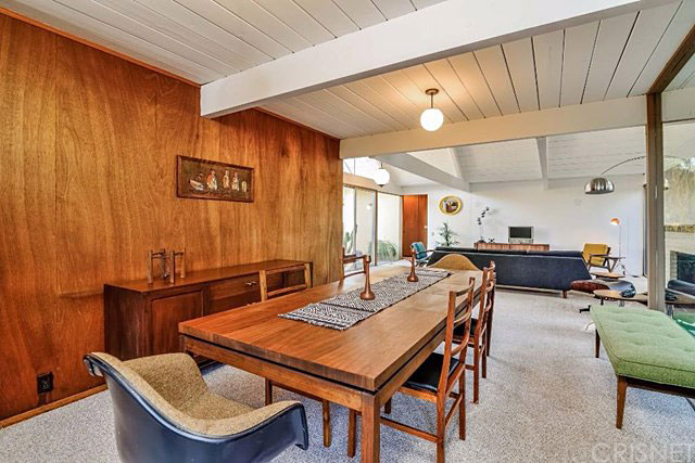 The living room flows into the dining room, which flows into the kitchen via a semi-open wall with a cooktop are and built-in seating. And all three of these rooms open to the backyard.