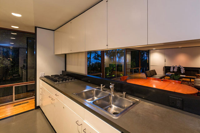 Though the home features some updates, such as modern appliances, it's an otherwise beautifully preserved version of the original. The galley style kitchen can be entered from two sides and features an expansive opening in the wall, which connects it visually to the huge living/dining room area.