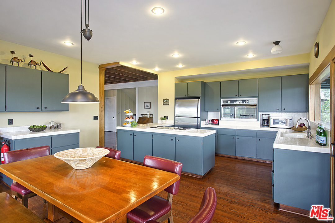 This eat-in kitchen is the bomb. The open workspace features a vintage oven and stove built into a countertop which wraps around on four sides and looks out into the foyer, allowing you to manage your meals while simultaneously welcoming arriving guests.