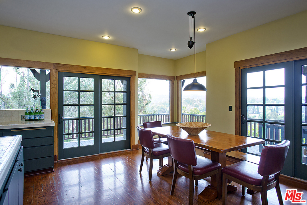 The breakfast area of the kitchen, which is large enough to be a full dining room, enjoys an abundance of natural light thanks to the windows and French doors that line two sides of the room. It this room hasn't satisfied your thirst for a cozy eating area, just step through the French doors...
