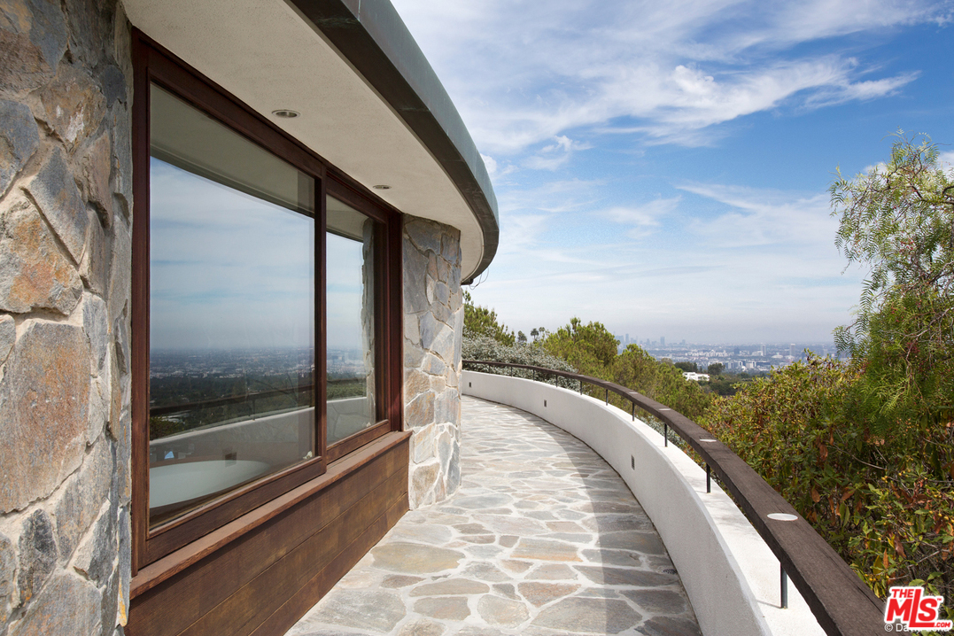 Situated on 4.33 acres, the home rests well above the treetops for breathtaking panoramic views of the canyon, city and beyond to the ocean.