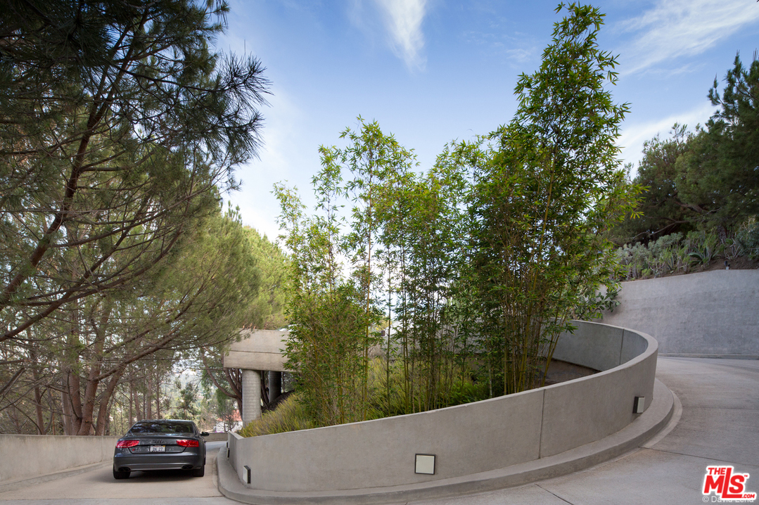 The property is accessed by ascending a private gated drive, itself a multi-million dollar project, which wraps around the hillside and leads to a spacious entry motor court.